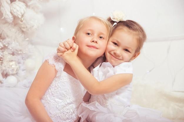 新年の装飾が施されたクリスマスツリーの近くの白いドレスの2人の少女
