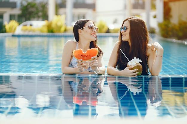 2人の女の子が日焼けし、プールで果物を食べる