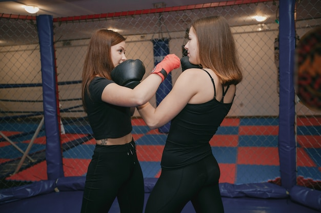 2人の女の子がジムでボクシングに従事している