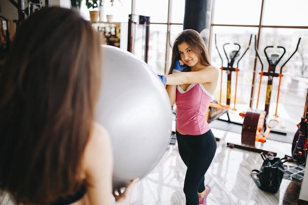 2つの美しい運動の女の子がジムに従事しています