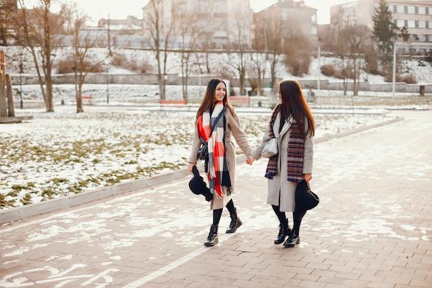 2人のおしゃれな女の子が街で休憩をとる