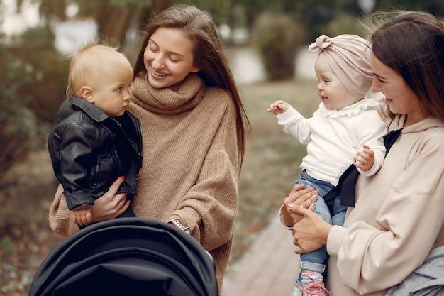 馬車で秋の公園を歩く2人の若い母親