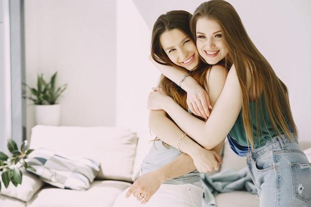 2人のファッションの女の子が家で楽しんでいます