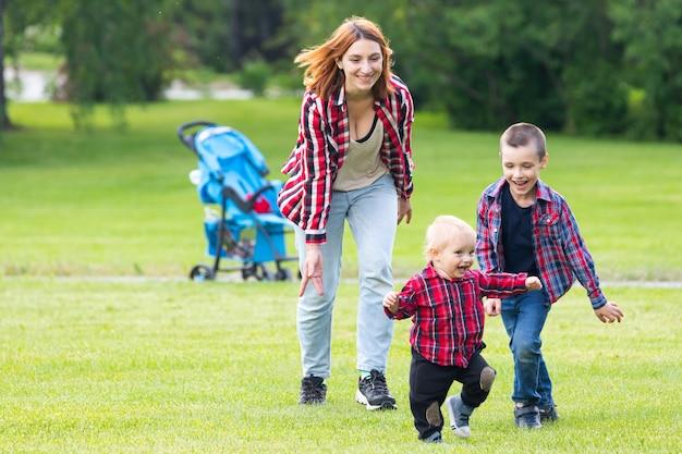 かわいい陽気な2人の男の子の兄弟の子供を持つ母親は公園で野外で遊ぶ。