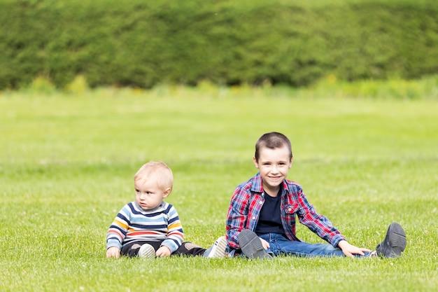 草の上に座って、年齢の異なる2人の陽気な兄弟が楽しく遊ぶ