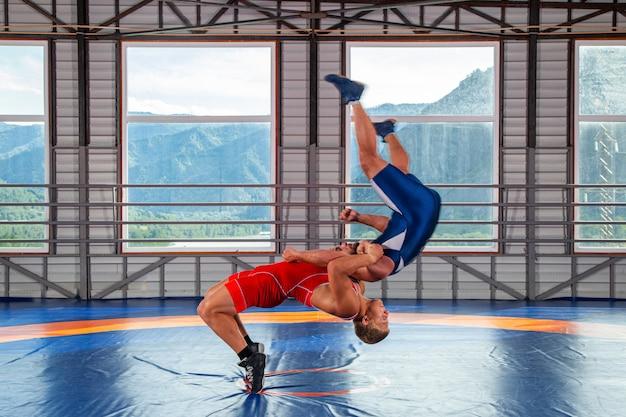青と赤のレスリングタイツを着た2人の若い男性がレスリングし、サプレックスレスリングをしています