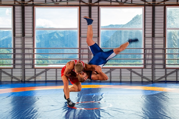 赤と青のユニフォームを着た2人のグレコローマンレスラーが、ジムのレスリングカーペットに太ももを投げます。