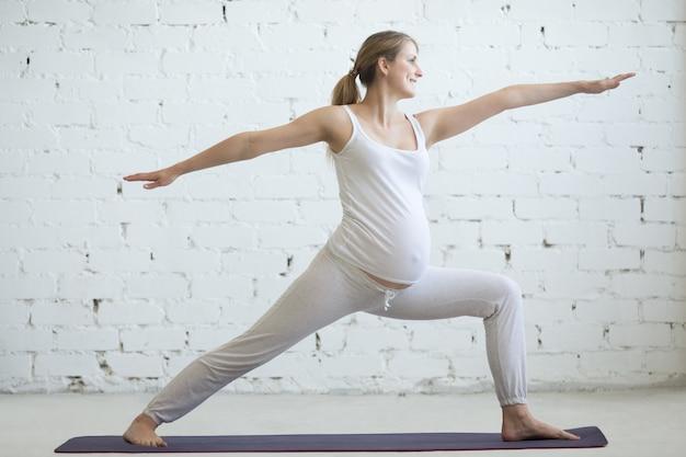 妊婦のヨガをやっている妊娠中の若い女性。戦士2ポーズ