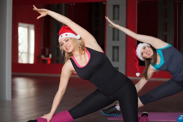 サンタクロースの帽子を着た2人のかわいい女の子がフィットネスセンターのマットで体を曲げます