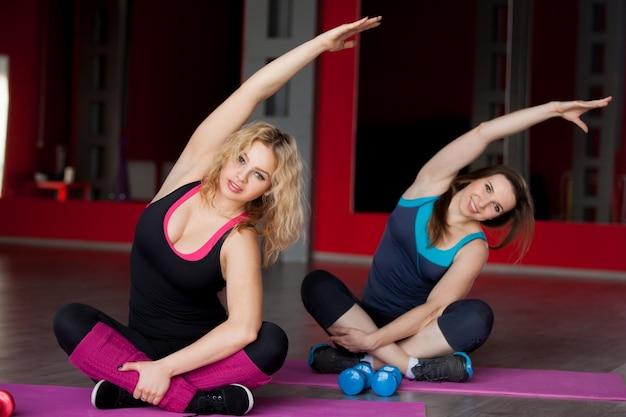 2人のかわいい女の子がフィットネスセンターのマットで体を曲げる