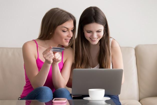 インターネットで商品を注文する2人の幸せなガールフレンド