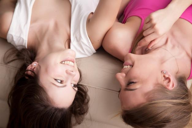 2人の若い笑顔のガールフレンドがソファーに横になっているとチャット。