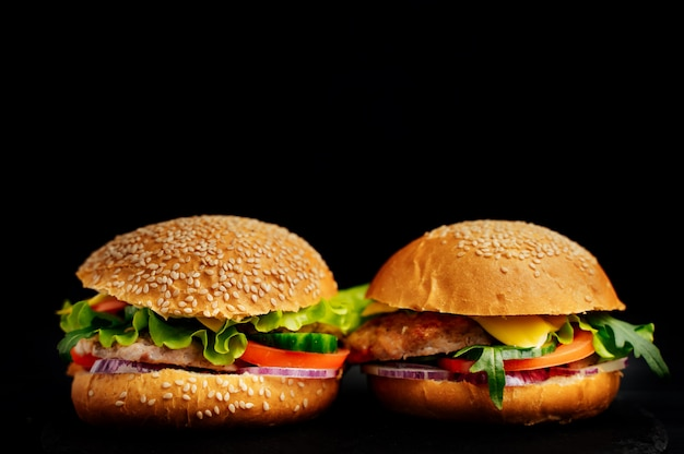 黒に分離された2つの新鮮なおいしいサンドイッチ