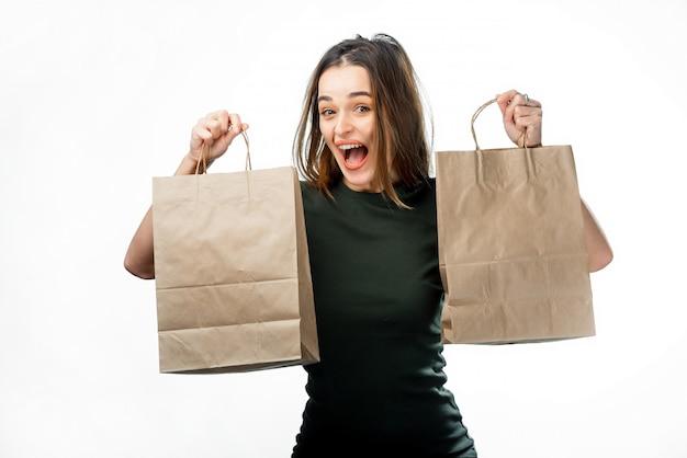 Счастливая довольная женщина с темными волосами держа 2 бумажных пакета. возбужденных привлекательная дама в футболке с удовольствием во время покупок.