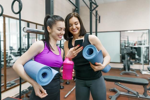 2 молодых усмехаясь женщины фитнеса разговаривая с циновками спорта