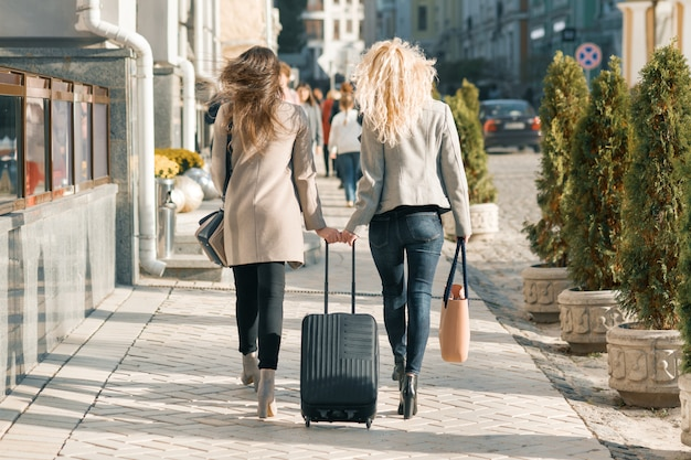 通りを歩いているスーツケースを持つ2人の若い女性