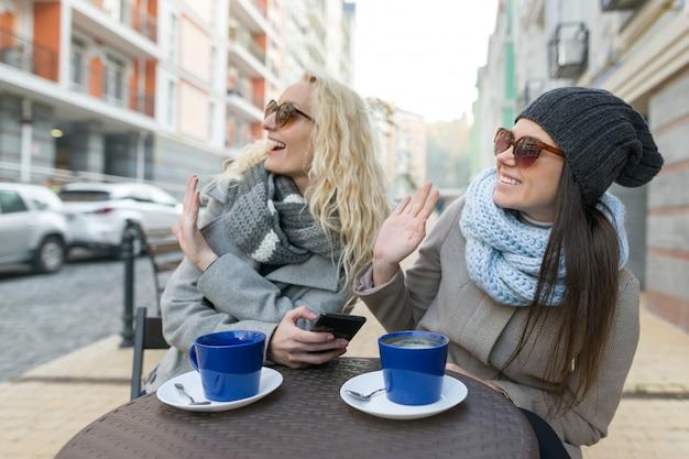 屋外カフェで2人の若い女性