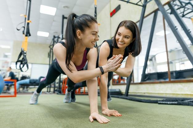 2 молодых здоровых женщины работая совместно в спортзале