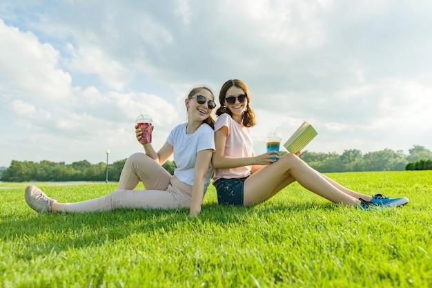 緑の芝生の上に座っている2つのガールフレンドのティーンエイジャー