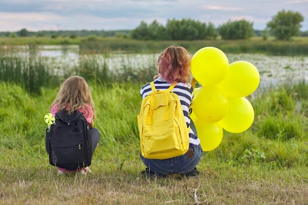自然に戻って風船を持つ2人の女の子、湖の近くの子供たち