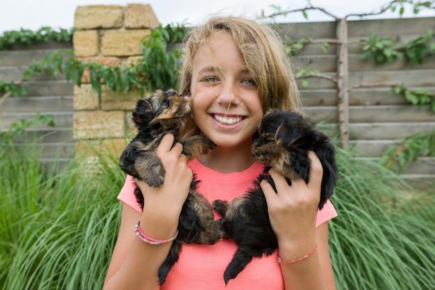 2つのヨークシャーテリアの子犬を保持している幸せな女の子