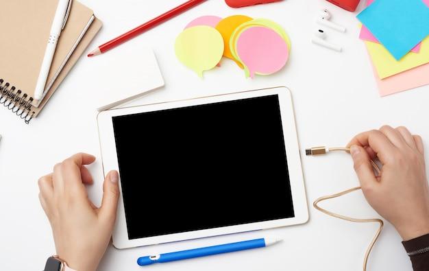 白い電子タブレットと2つの手、画面上での作業または描画のプロセス、ノートブックを備えた職場
