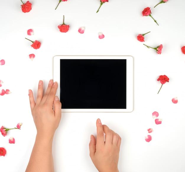 ピンクのバラのつぼみと白でデバイスを保持している2つの女性の手