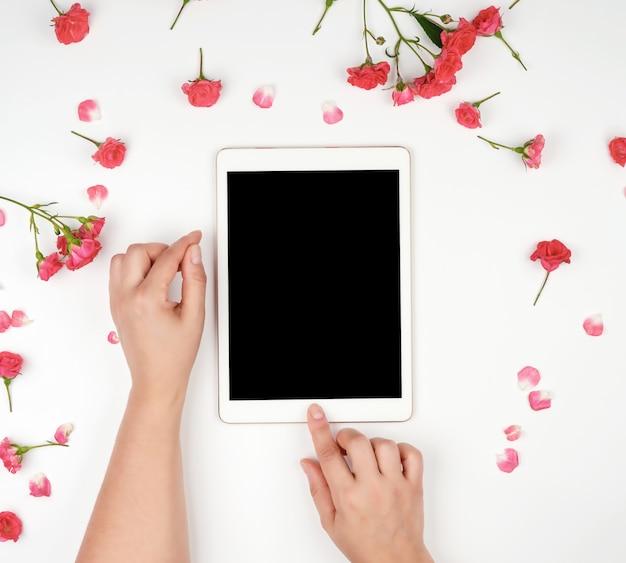 空白の黒い画面とデバイスを保持している2つの女性の手を持つ白い電子タブレット
