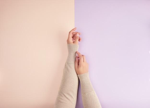 グリーンピンクの背景に光の滑らかな肌を持つ2つの女性の手