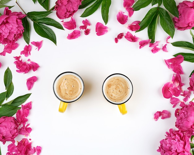 白いテーブルの上のコーヒーと2つの黄色のセラミックカップ