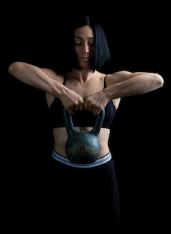 黒い髪と2つの手で金属の重量を上げると運動美少女