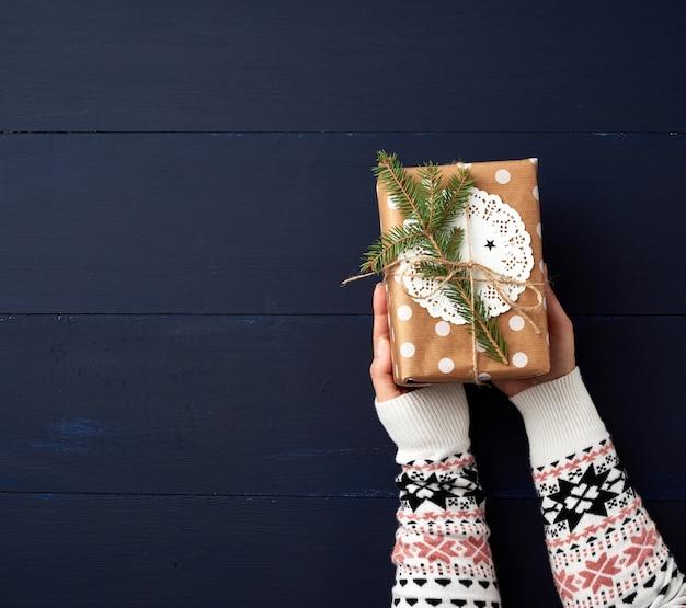 2 женских руки держат бумажную закрытую коробку на голубом деревянном. праздничная концепция