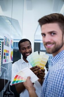 色見本を固定している2つの男性のグラフィックデザイナー