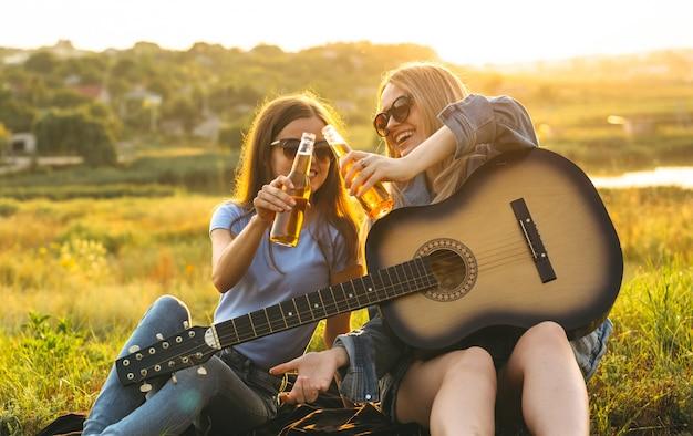 サングラスをかけた2人の陽気な女の子と若い友人、ビールを飲み、日没で一緒に過ごした時間を楽しんでいます。