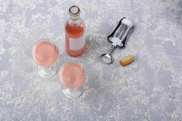 ローズワインのテイスティングレイアウト。開いたボトル、グラス2杯、灰色の背景にローズワインとコルク栓抜き。