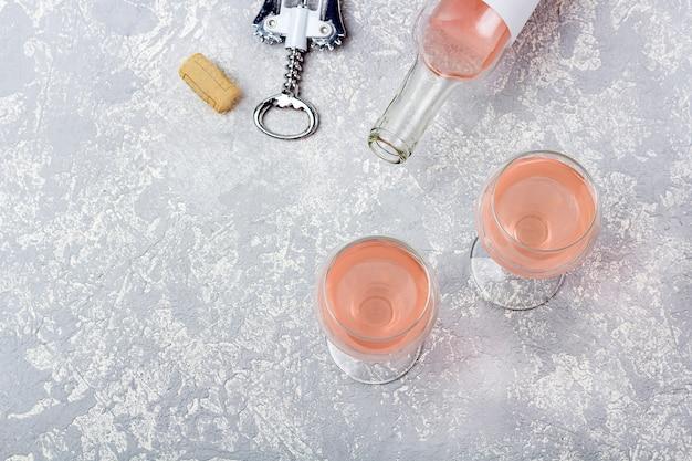 ローズワインのテイスティングレイアウト。開いたボトル、グラス2杯、灰色の背景にバラのワインとコルク栓抜き。