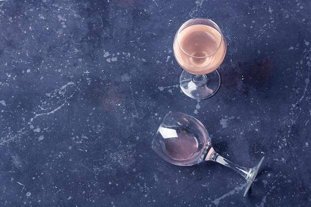 暗い背景にバラのワインを2杯。半分空のガラスが横になっています。ワイン試飲会。酔いのコンセプト。