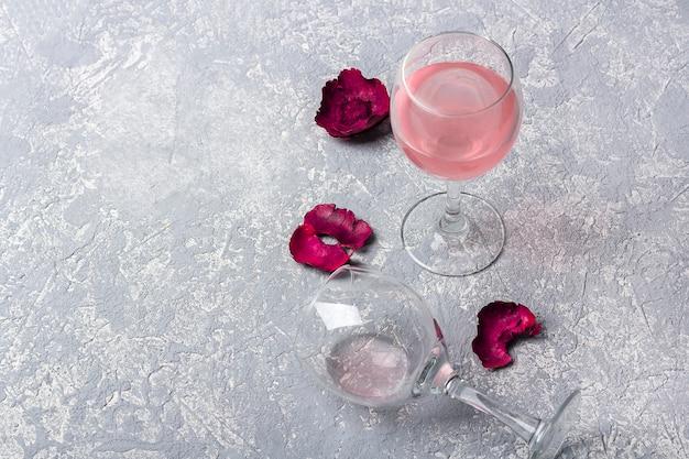 灰色の背景にバラのワインと赤いバラの花びらを持つ2つのメガネ。半分空のガラスが横になっています。ワイン試飲会。酔いのコンセプト。