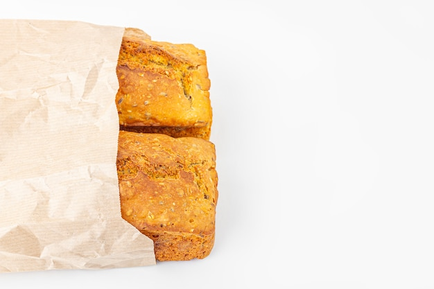 2 хлебца цельнозернового хлеба в эко мешок на белом фоне. свежеиспеченный домашний квадратный хлеб. концепция органического и вегетарианского питания