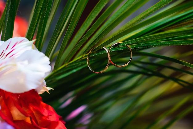 2つの金の結婚指輪が花束の葉に掛かっています。