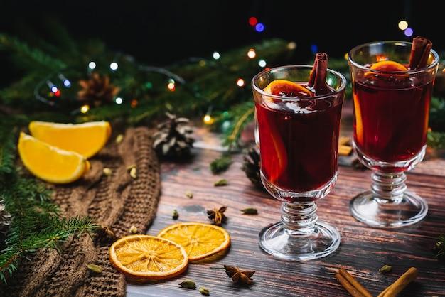 クリスマスの2杯は、スパイスと木製の素朴なテーブルにオレンジスライスとホットワイン