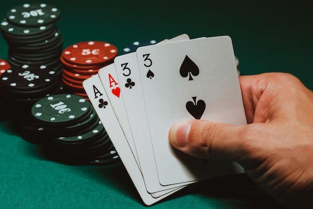 ゲームチップの背景にあるギャンブラーの手でポーカーの2ペアのカード