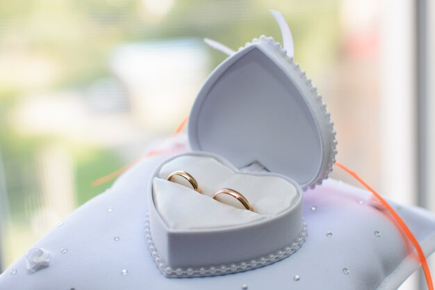 白いボックスにある2つの金の結婚指輪