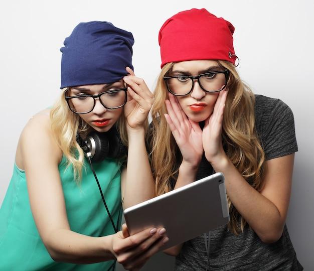 流行に敏感な2人の女の子の友人がデジタルタブレットを使用