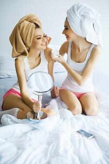 お風呂の後ベッドに座っている完璧な肌を持つ2人の陽気な姉妹