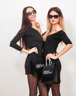 黒い金曜日の休日に買い物袋を示す2人の若い笑顔の女性