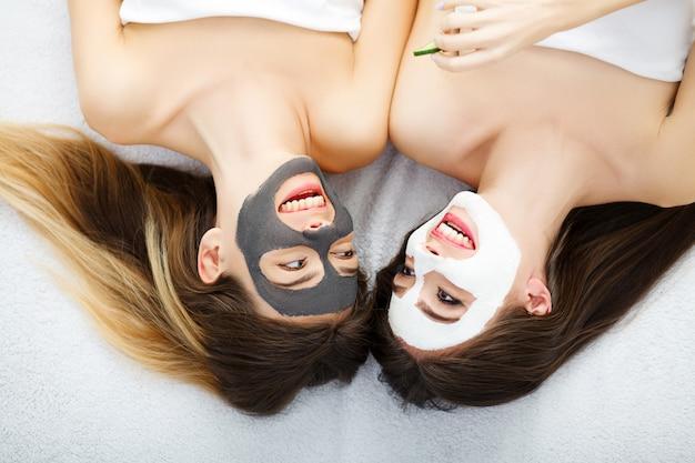カメラを見て、床に向かい合って横になっている笑顔の顔に顔のクリームを持つ2つの美しい女の子の肖像画