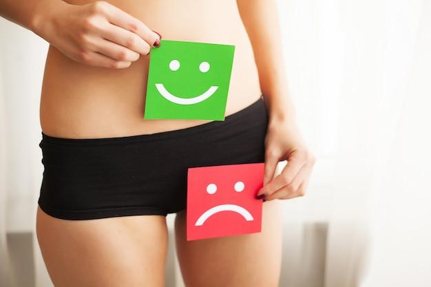 女性の健康問題。彼女の胃の近くの悲しい笑顔と幸せそうな顔で2つのカードを保持しているパンティーでフィットスリムなボディを持つ女性のクローズアップ。消化器疾患、痛み、健康上の問題