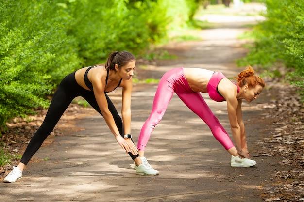 フィットネス。夏の公園で屋外の足を伸ばして2人の女性ランナー