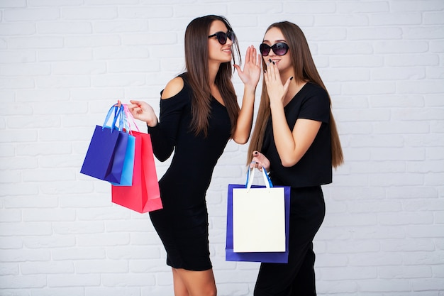 ショッピング。黒い金曜日の休日に明るい背景に黒い袋を保持している2人の女性